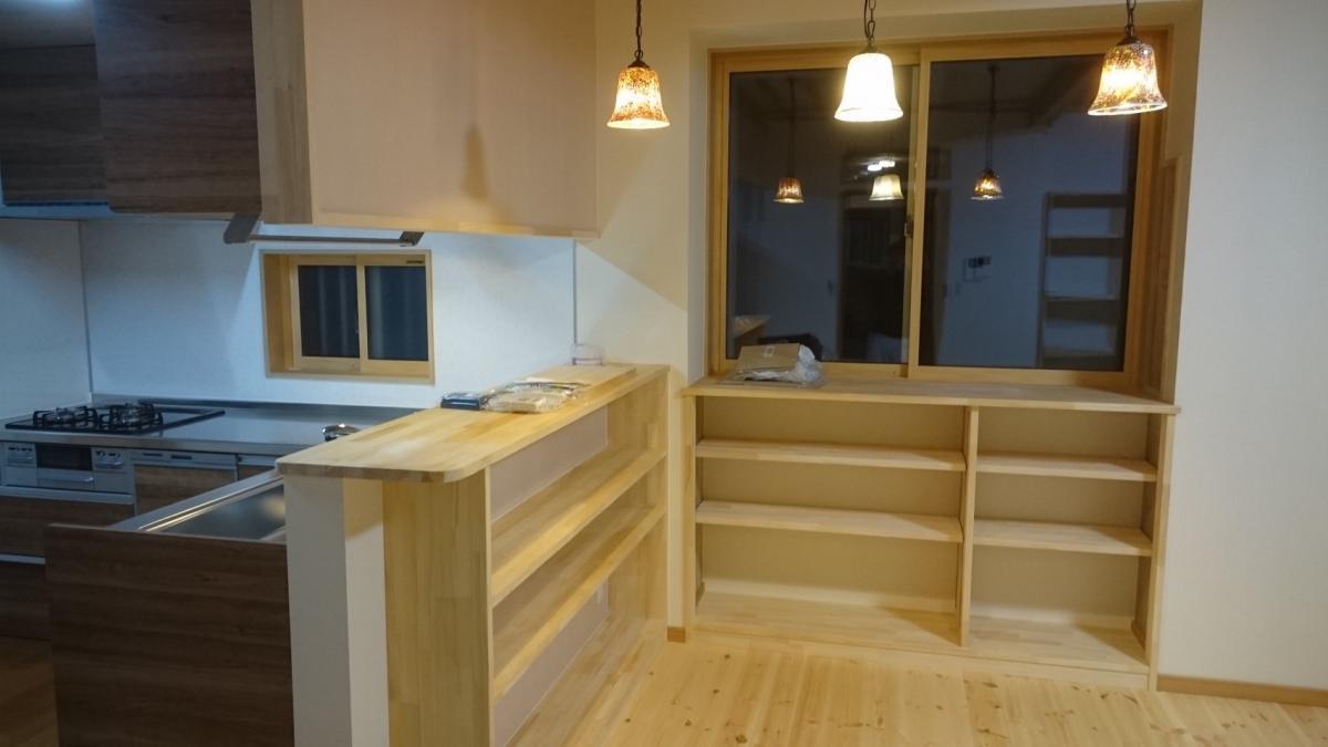 リビングとつながるキッチン。カウンターの下も有効活用し収納棚に。こだわりの照明と天然木の相性も抜群です。